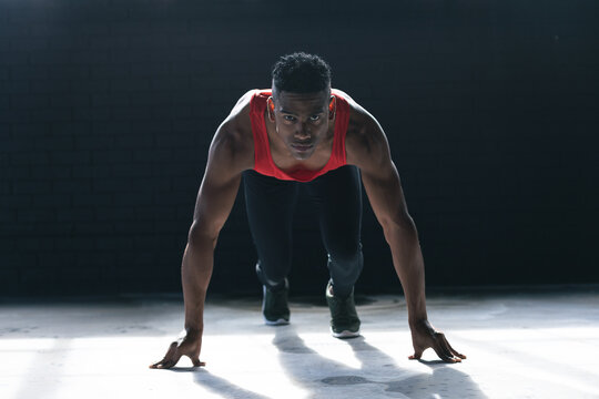African american man wearing sports clothes kneeling starting to run in empty urban building