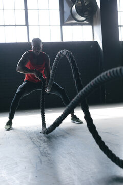 African american man wearing sports clothes battling ropes in empty urban building