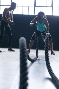 African american woman wearing sports clothes battling ropes in empty urban building