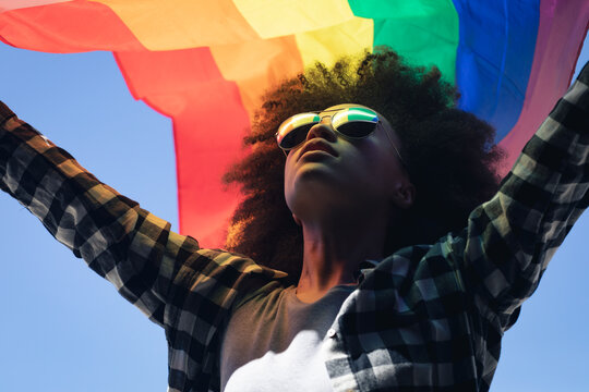 Mixed race woman standing on rooftop holding rainbow flag