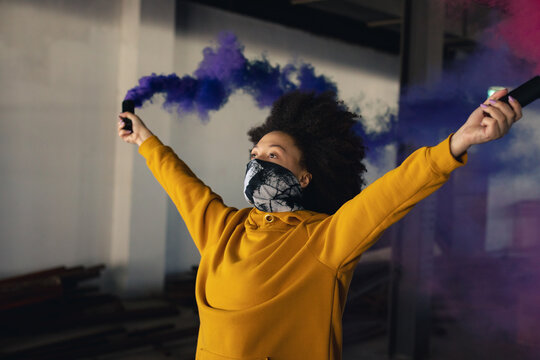 Mixed race woman wearing face mask holding a blue flare