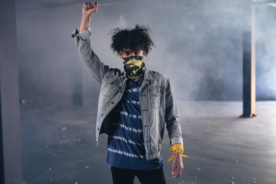 Mixed race man in an empty building wearing face mask raising fist