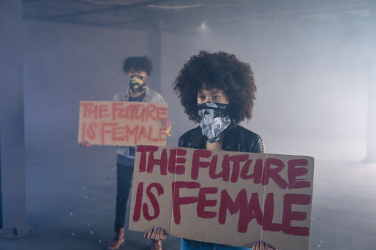 Mixed race man and woman wearing face masks holding protest signs