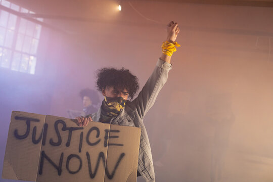 Mixed race man wearing face mask holding protest sign raising fist