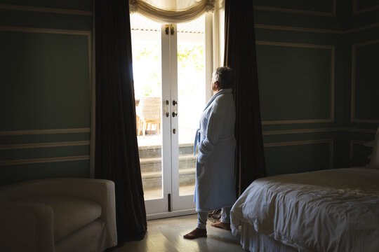 Senior african american woman standing by a window in a sleeping room