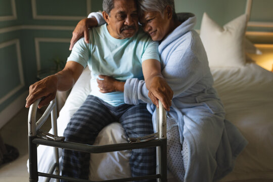 Senior african american couple sitting on a bed hugging in a sleeping room