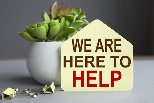 we are here to help. text on yellow sticker on gray background