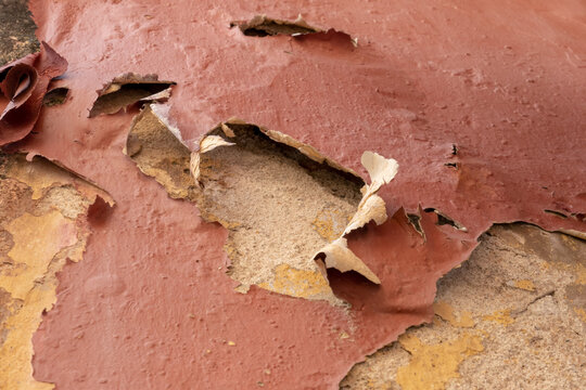 Closeup of old red paint peeling off an ancient wall