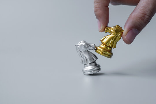 businessman hand moving gold Chess Knight (horse) ``figure and Checkmate enermy or opponent during chessboard competition. Strategy, Success, business planning, interruption and leadership concept