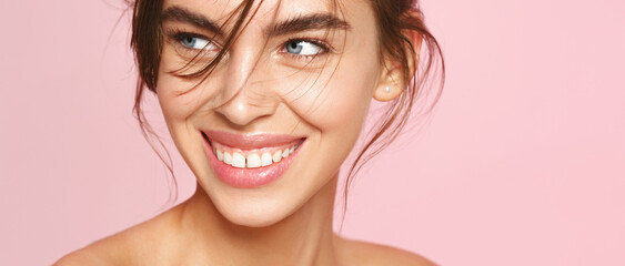 Close-up of fresh natural woman with nude makeup, white smile, looking aside on pink background....
