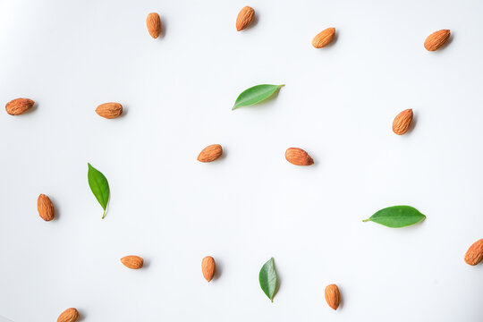 pattern of almonds nuts and green leaves arrange on white background
