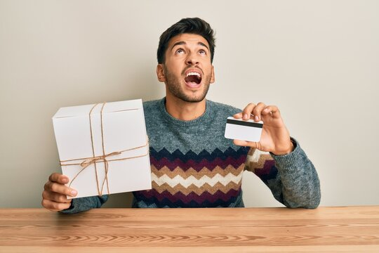 Young handsome man holding gift and credit card angry and mad screaming frustrated and furious, shouting with anger looking up.