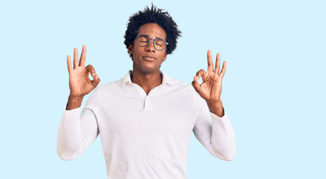 Handsome african american man with afro hair wearing casual clothes and glasses relaxed and smiling with eyes closed doing meditation gesture with fingers. yoga concept.