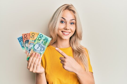 Beautiful caucasian blonde girl holding australian dollars smiling happy pointing with hand and finger