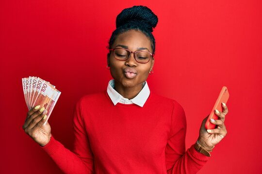 Young african american woman using smartphone holding norwegian krone banknotes looking at the camera blowing a kiss being lovely and sexy. love expression.