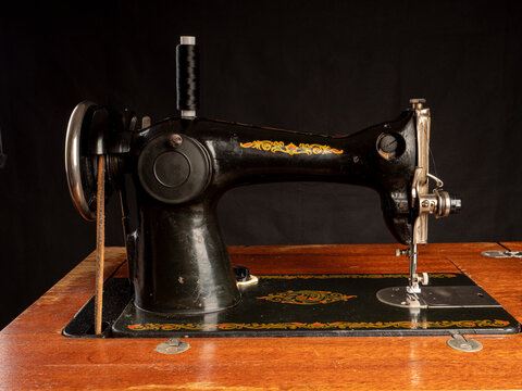 Soviet black sewing machine on a wooden stand close-up