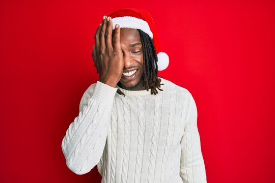 African american man with braids wearing christmas hat covering one eye with hand, confident smile on face and surprise emotion.