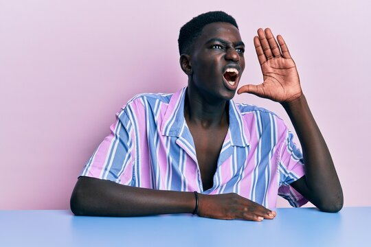 Young african american man wearing casual clothes sitting on the table shouting and screaming loud to side with hand on mouth. communication concept.