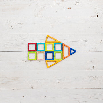 Arrow made of magnetic plastic parts of the constructor on a white wooden background