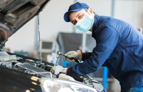 Mechanic repairing a car, covid concept