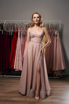 Young beautiful blonde girl wearing a full-length pale pink glitter chiffon draped prom ball gown. Model selecting an outfit for occasion in dress hire service with many options on background.