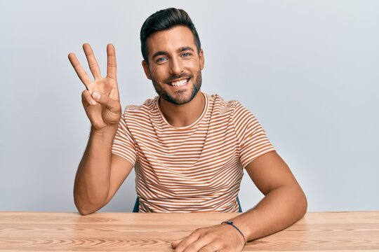 Handsome hispanic man wearing casual clothes sitting on the table showing and pointing up with fingers number three while smiling confident and happy.
