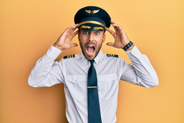 Fototapeta Handsome hispanic man wearing airplane pilot uniform crazy and scared with hands on head, afraid and surprised of shock with open mouth obraz