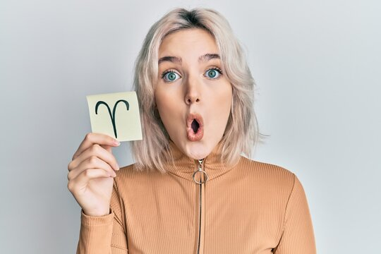 Young blonde girl holding paper with aries zodiac sign scared and amazed with open mouth for surprise, disbelief face