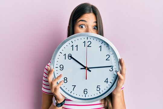 Young brunette woman holding big clock covering face celebrating crazy and amazed for success with open eyes screaming excited.