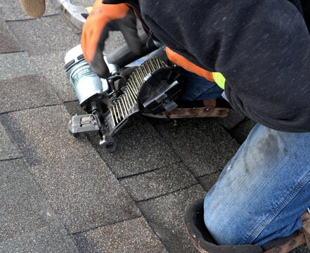 Roofer on a residential roof, checks the nails in his pneumatic nail gun before proceeding with repairs.