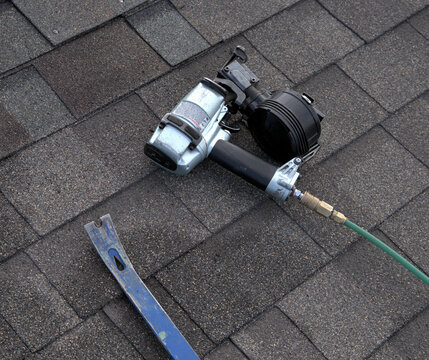 Two tools used by a professional roofer: pry bar to loosen nails and remove damaged shingles; nailg un to secure new shingles in place.