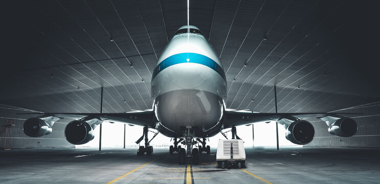 Airplane parking in a hanger inside airport . Elements of this image furnished by NASA