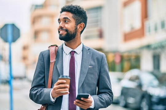 Young african american businessman using smartphone and drinking take away coffee at the city.