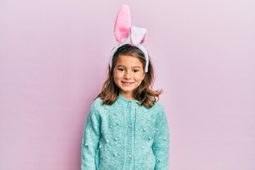 Little beautiful girl wearing cute easter bunny ears with a happy and cool smile on face. lucky...