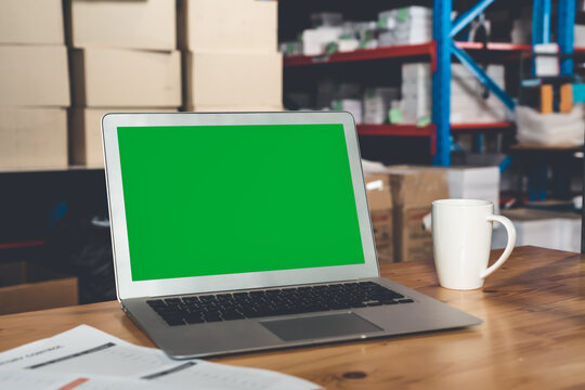 Computer with green screen display in warehouse storage room . Delivery and transportation software concept .