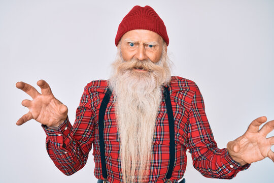 Old senior man with grey hair and long beard wearing hipster look with wool cap smiling funny doing claw gesture as cat, aggressive and sexy expression