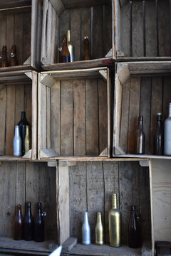 Vertical shot of Painted wine bottle decorative wall with vintage wood crates