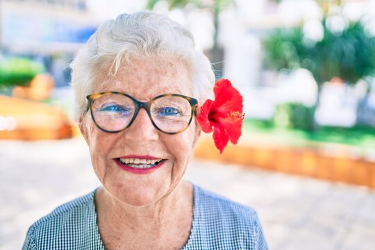 Elder senior woman with grey hair smiling happy outdoors wearing a decorative flower