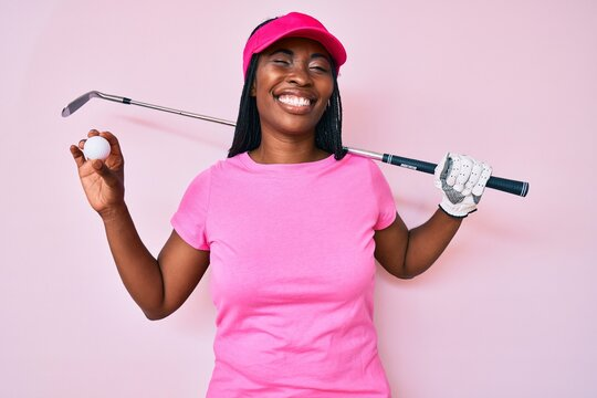African american golfer woman with braids holding golf ball winking looking at the camera with sexy expression, cheerful and happy face.