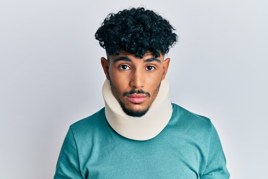 Young arab handsome man wearing cervical neck collar with serious expression on face. simple and natural looking at the camera.