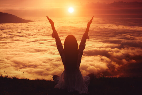 A woman with her arms outstretched meets the dawn in the mountains against the background of the sky and the sun disk. A woman practices yoga in the mountains.