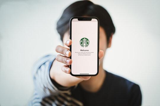 Chiang Mai, Thailand Jan 23, 2021,Hand holding smart phone opening online menu page of Starbucks website, Starbucks coffee shop.