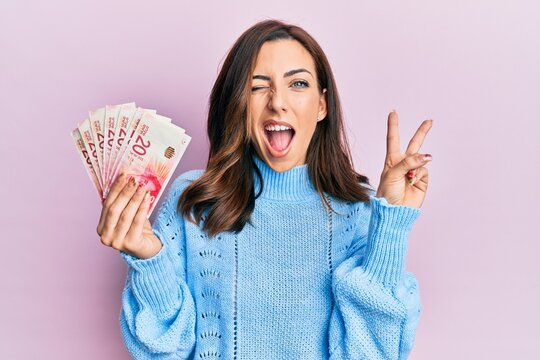 Young brunette woman holding 20 israel shekels banknotes smiling with happy face winking at the camera doing victory sign with fingers. number two.