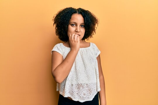 Young little girl with afro hair wearing casual clothes looking stressed and nervous with hands on mouth biting nails. anxiety problem.