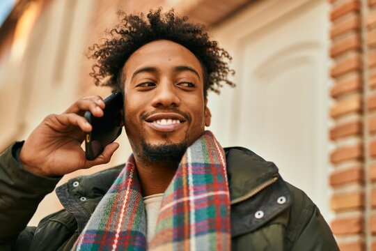Young african american man smiling happy talking on the smartphone at the city
