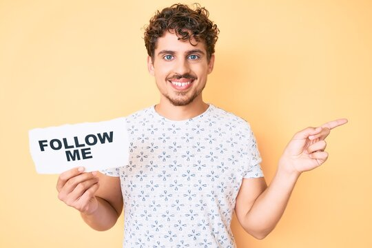Young caucasian man with curly hair holding follow me message paper smiling happy pointing with hand and finger to the side