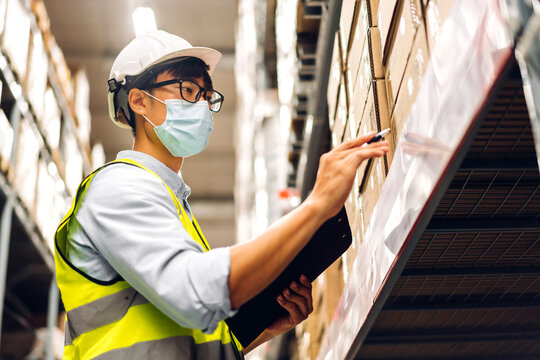 Portrait of asian engineer man in helmets in quarantine for coronavirus wearing protective mask order details checking goods and supplies on shelves with goods background in warehouse
