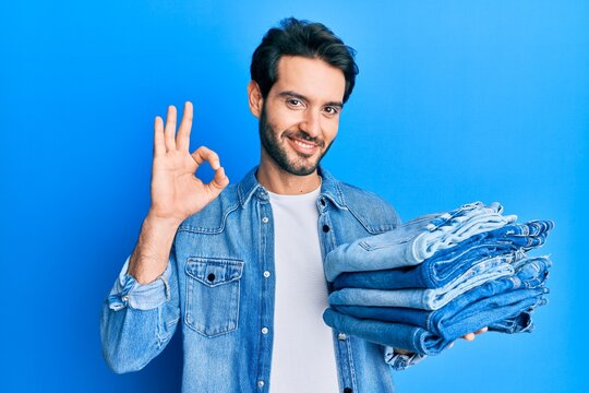 Young hispanic man holding stack of folded jeans doing ok sign with fingers, smiling friendly gesturing excellent symbol