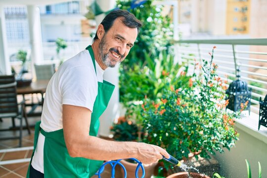 Middle age man with beard smiling happy watering the plants at the terrace