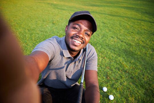 Black golfer takes a selfie on an outdoor golf course.